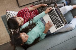 Children on couch working on laptop
